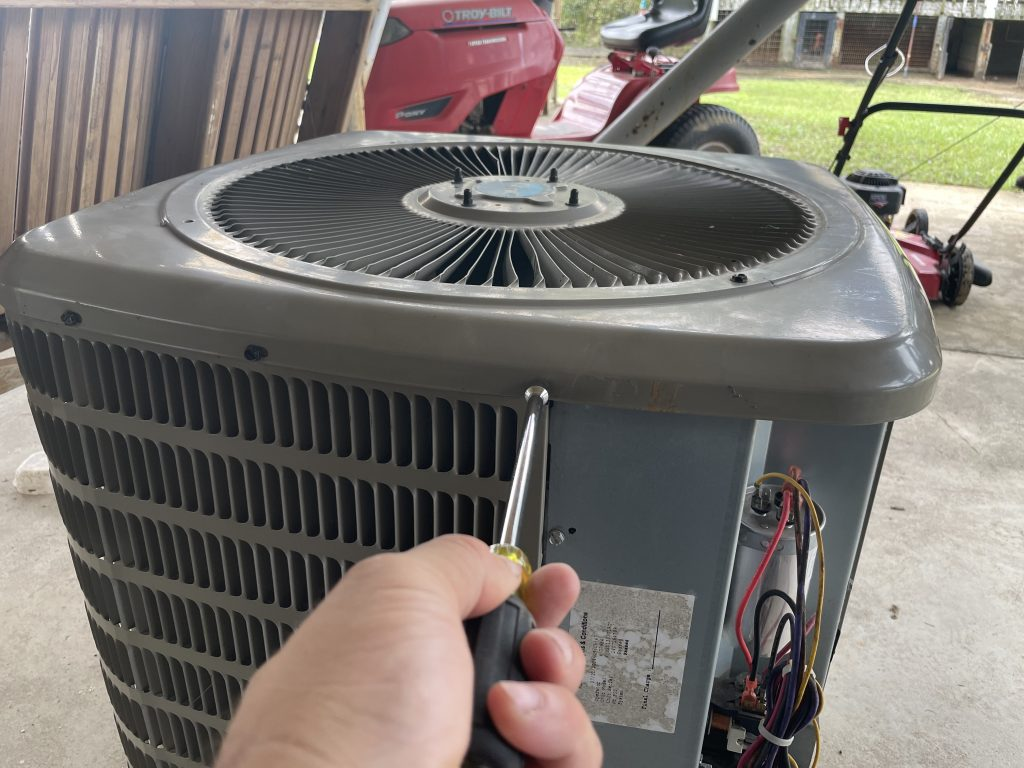 Start taking the screws out of the top of the condenser in order to replace the condenser fan motor